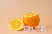 Close-up photo of cut orange and melting ice cubes isolated on sandy background