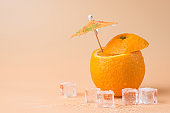 Summertime relax concept. Close-up photo of cut orange with a cocktail umbrella in it and ice cubes isolated on sandy background