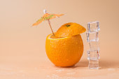 Close-up photo of cut orange with a cocktail umbrella in it and a stack of ice cubes isolated on sandy background