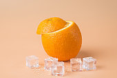Photo of tasty yummy fresh cut orange fruit with ice cubes isolated over beige yellow background with copyspace