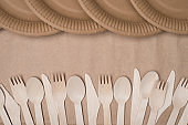 Top above overhead view photo of rows of wooden cutlery and paper plates isolated on craft paper background table