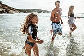 Family running and splashing on the beach