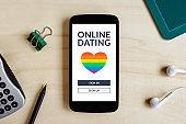 LGBT dating app concept on mobile phone over wooden desk