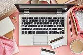 Online shopping concept on pink desk