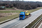 Transportation Tow truck or Flatbed truck on a highway carrying a construction machine
