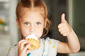 Cheerful smiling child girl eating a delicious cake and showing thumbs up. mouth in cream. Cheerful carefree childhood