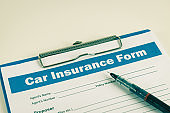Car Insurance Claim Form or Insurance Document and Pen at Right Frame in Vintage Tone