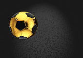 Gold soccer ball on dark background.