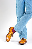 Closeup of Crossed Mens Legs in Brown Oxford Brogue Shoes. Posing in Blue Jeans Against White Background. Vertical Image