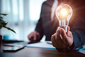 businessman hand holding light bulb with finance document and tool,concept of New ideas for business and fonance.