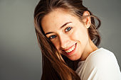 Close-up portrait of a smiling young girl in a white shirt on a gray background. in a good mood. Without retouching and makeup.