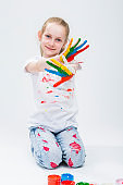 Smiling Active Caucasian Young Girl With Messy Colorful Palms While Making Handprints On T-Shirt With Hands Crossed In Front. Against White Background. Vertical image