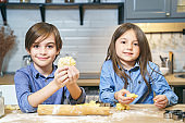 Portrait of cute smiling kids boy and girl preparing cookies from dough in the kitchen