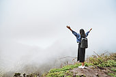 Young woman tourist with backpack relaxing on top of a mountain and enjoying the view of the misty valley