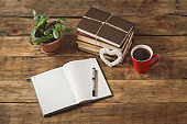 Discounted Diary, Heart, Flower, Pile of Books, Red Cup with Coffee or Tea, Pen on a wooden Table. Photographed under natural light
