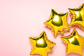 Gold foil shaped star air balloons on pink background. Concept of a holiday and celebration. The concept of party decoration, wedding, anniversary, birthday, greeting card. Metallic balloons. Banner