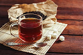 Cup with Tea, Dried Tea Leaves on Kraft Paper, Sugars of Sugar and Spoon on a Wooden Table