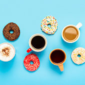 Tasty donuts and cups with hot drinks, coffee, cappuccino, tea on a blue background. Concept of sweets, bakery, pastries, coffee shop, meeting, friends, friendly team. The square. Flat lay, top view