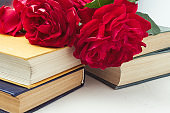 A bouquet of red roses on a pile of books on a light stone backg