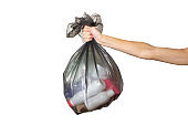 Female hand holds a trash bag with garbage on a white isolated background. Separate trash concept, stop plastic