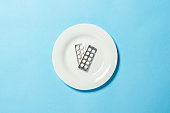Two plates with pills on a white plate on a blue background. Insomnia, a choice of drugs, vitamins, weight loss through farm drugs. Flat lay, top view