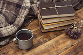 Amazing Image of a Metallic Cup with Hot Tea, Coffee, Warm Plaid, A Pile of Books Tied with a Rope on a Wooden Table