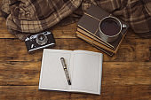 Diary with pen, books, aluminum vintage cup with hot tea and an old camera and plaid on a wooden background