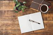 Picture of a diary and pens on a wooden table