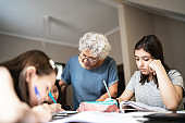 Grandmother helping granddaughter with homework while they studying at home