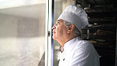 Senior chef looking through the window, daydreaming