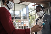 Receptionist measuring temperature of male employee at office's entrance - with face mask