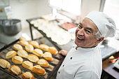 Portrait of a senior baker holding a tray full of bread