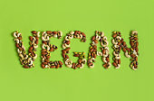 Word vegan made of nuts on a green background