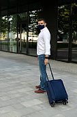 Man in casual clothes walking with a suitcase