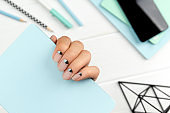 Groomed womans hand with creative nail design holding note pad