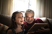 Grandfather and granddaughter using digital tablet at home