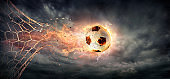 Fiery Soccer Ball breaking through The Net With Dramatic Sky