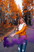 Artistic, Spooky, Dark, Colorful Portrait of a Teenage or Young Adult Caucasian Female Using a Purple Smoke Bomb in the Autumn Fall Colors Outdoors in the Grand Mesa National Forest near Grand Junction, Colorado