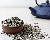 dried green tea leaves in a brown bowl with a blue Japanese teapot