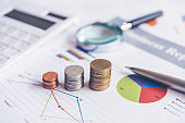 Growth economic on stack of coins on report paper analyze performance financial graph funding with calculate for investment business. Investment and Saving Concept