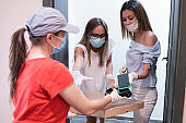 The New Normal. Delivery at home while coronavirus protection. Young women receiving pizza delivery at home and paying for it. Illness prevention during COVID-19 pandemic. People with protective mask on their faces.