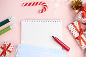 Notepad wish list on a pink table with felt-tip pens with protective face mask on a Christmas background with mock up. Concept of christmas, new year, plans and making wishes and corona virus