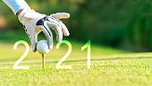 Golfer woman putting golf ball for Happy New Year 2021 on the green golf for new healthy.  copy space. Healthy and Holiday Concept.