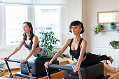 Two Young Women Doing Exercises on Pilates Reformer Bed at Gym