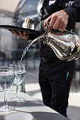 Pouring Water in Glass with Silver Carafe