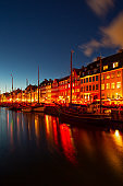 Cityscape at Night, Famous Nyhavn Pier with Colorful Buildings and Boats in Copenhagen, Denmark