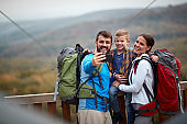 A happy family taking selfie on the top of a watchtower in the forest
