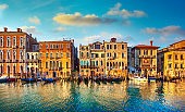 Venice, Grand Canal, gondolas and buildings at sunrise. Italy