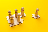 Wooden figures on puzzles on yellow background as a symbol of team building. Organization group people in business. Cooperation and partnership