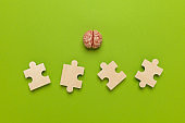 Human brain with a puzzle on green background. Business idea, memory loss, training and new skills